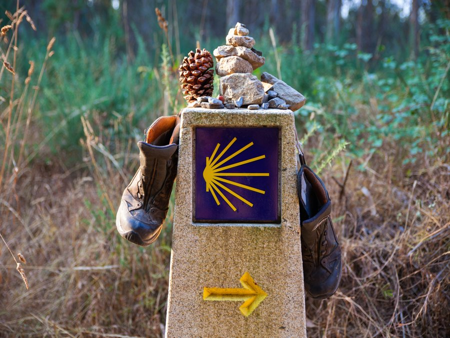 Hiking boots and stone on the stone signal, Symbol of the way of St. James, Camino de Santiago