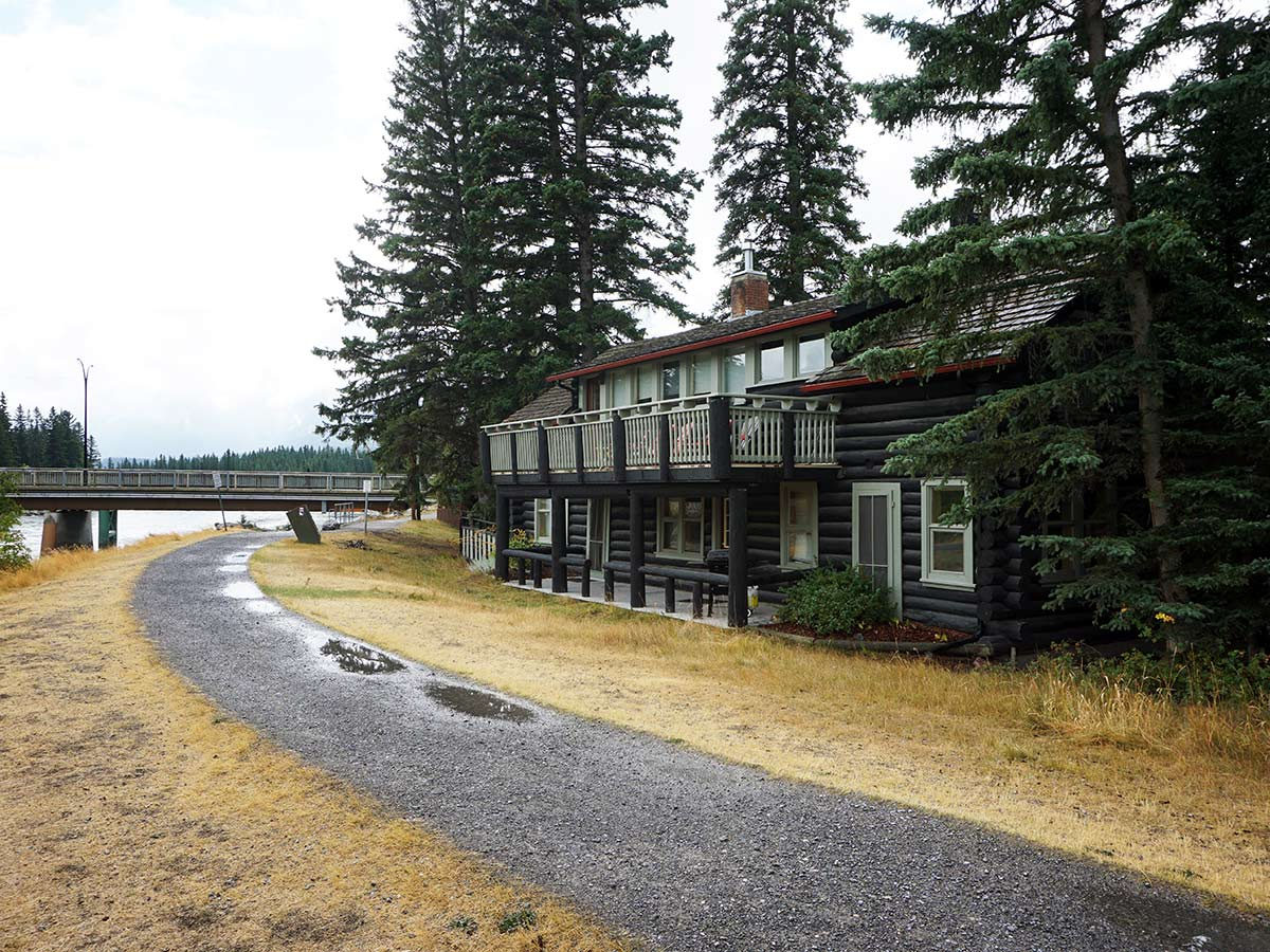 A beautiful old log cabin on the banks of the Bow River on the Main Street, Bow River and the Rail Bridge Hike in Canmore, Alberta