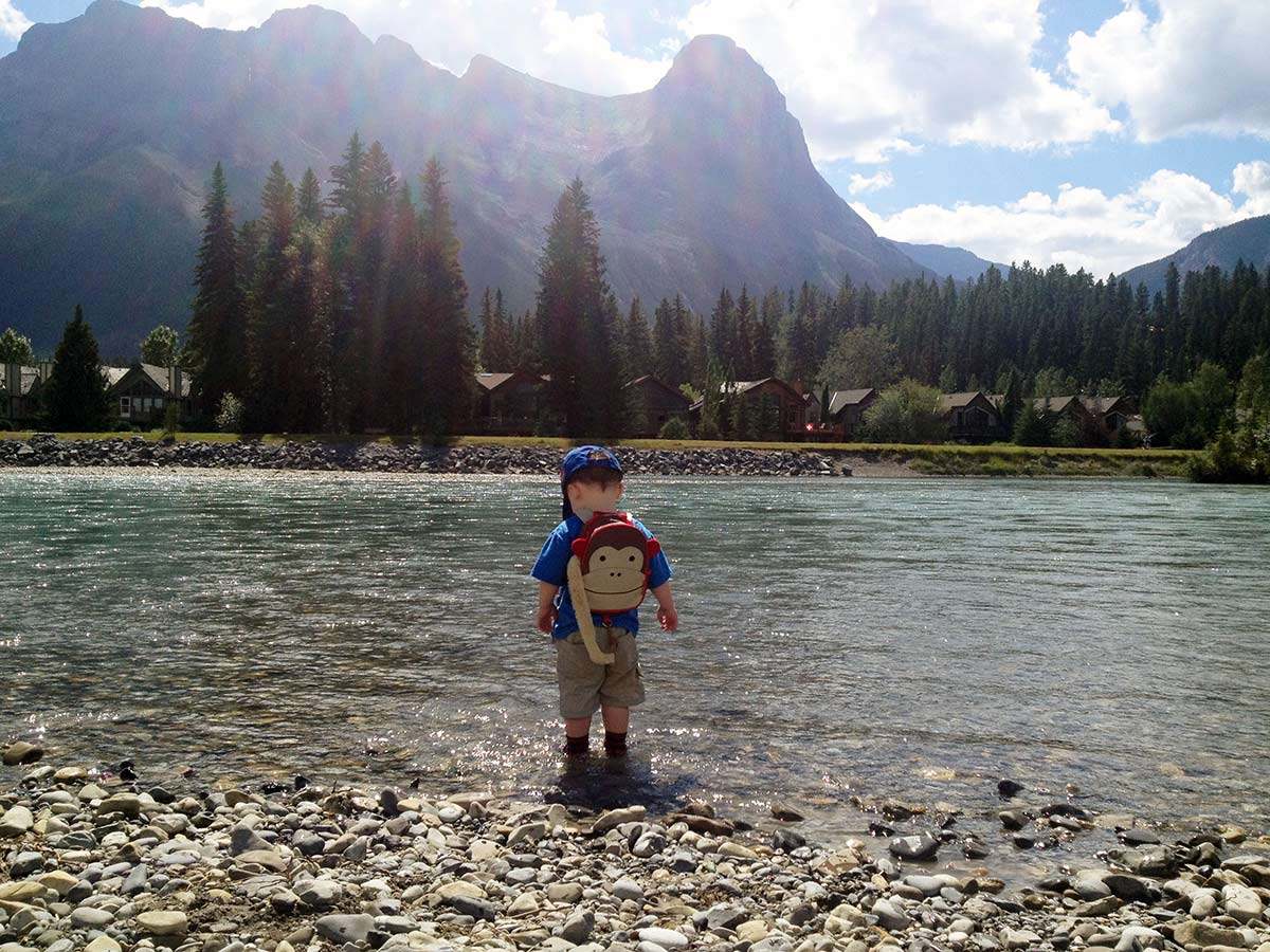 Throwing stones into the river on the Main Street, Bow River and the Rail Bridge Hike in Canmore, Alberta