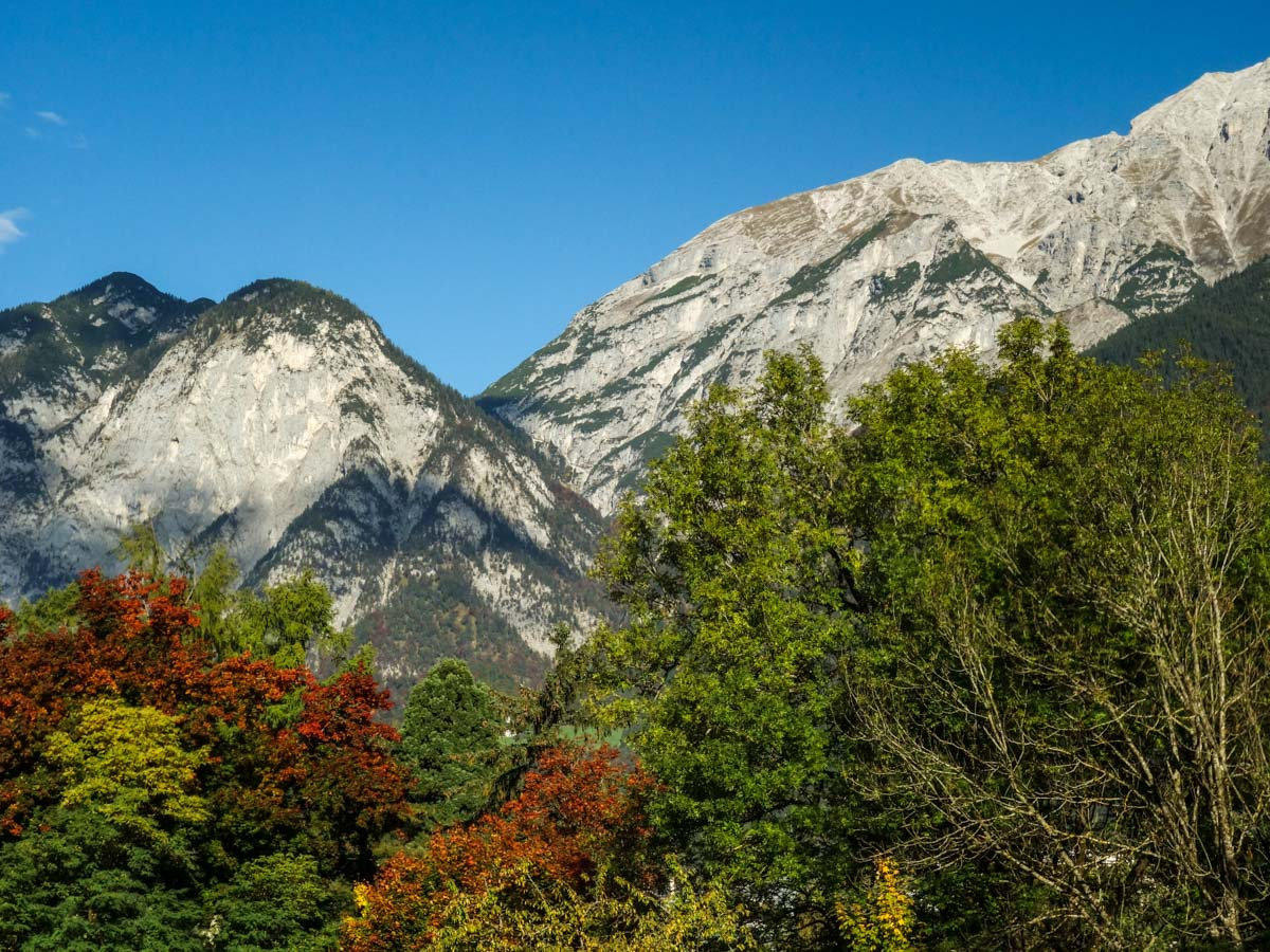 Colorful trees in front of the Nordkette mountain range on the Natterer See Hike from Innsbruck, Austria
