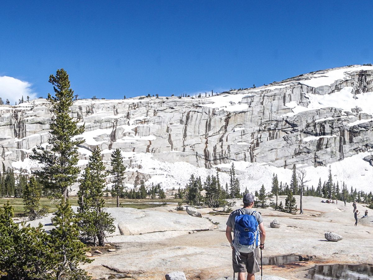 Man hiking near Cathedral Lakes with gear on his back in Yosemite