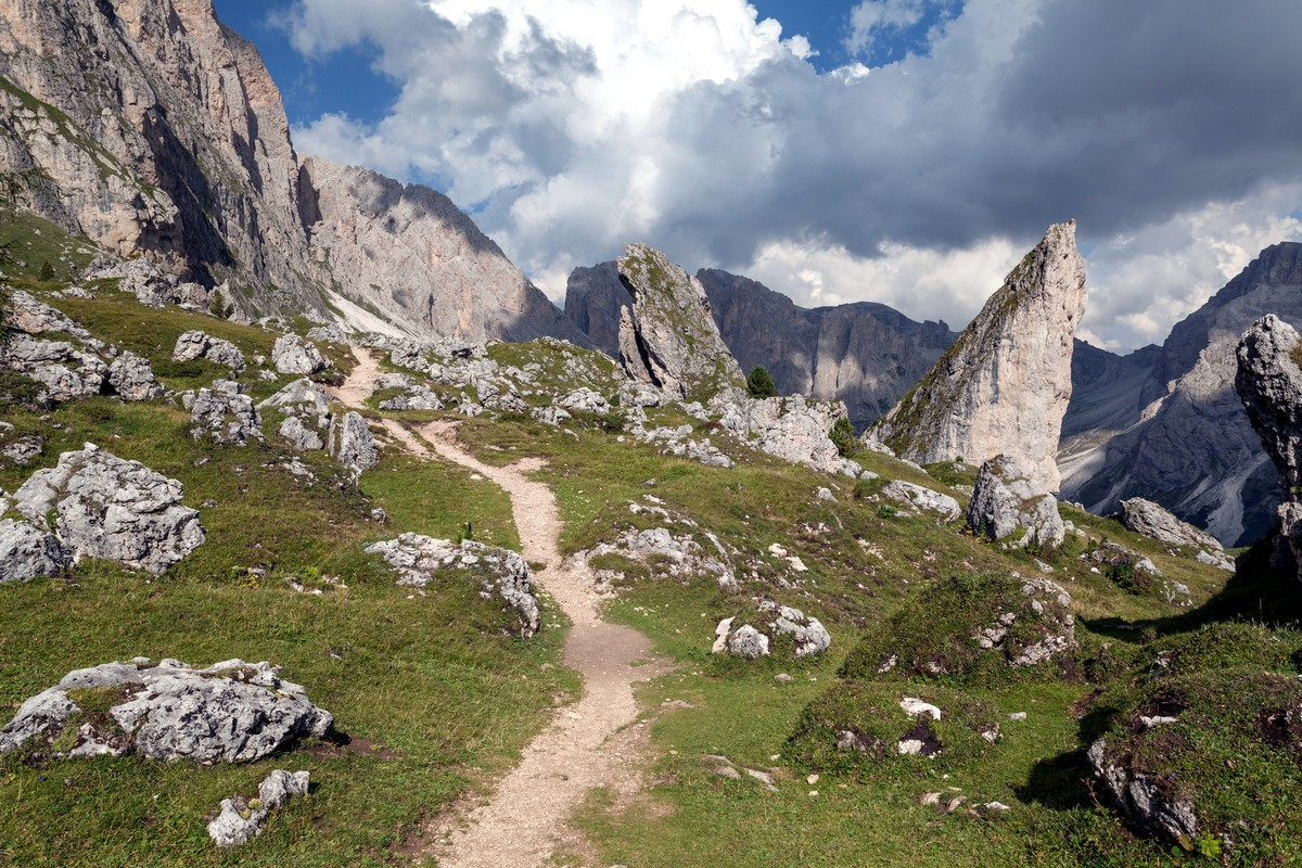 Path at the side of the mountains among rocks on the Seceda / Puez Odle Hike in Dolomites, Italy