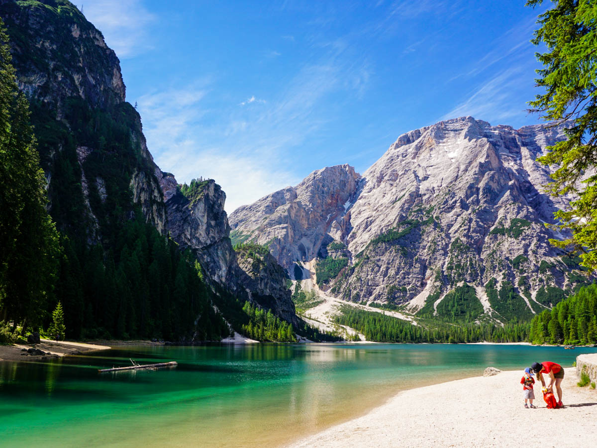 On the beach at the family friendly trail of the Lago di Braies Hike in Dolomites, Italy