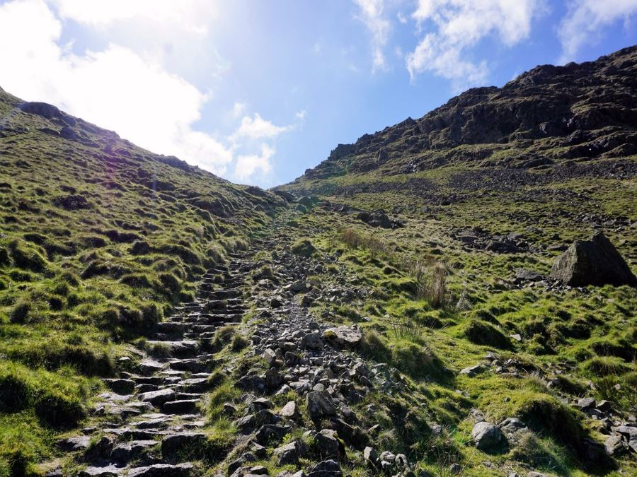 Climbing steps up to saddle below Thornthwaite Crag on the Roman High Street Circuit Hike in Lake District, England