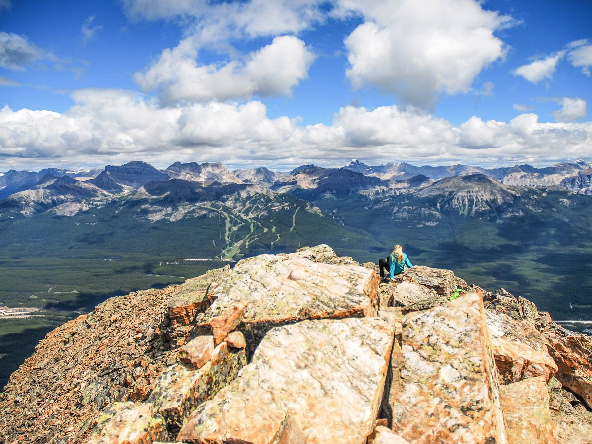 Woman sitting on top of a mountain at Mount Fairview Summit Hike in Lake Louise