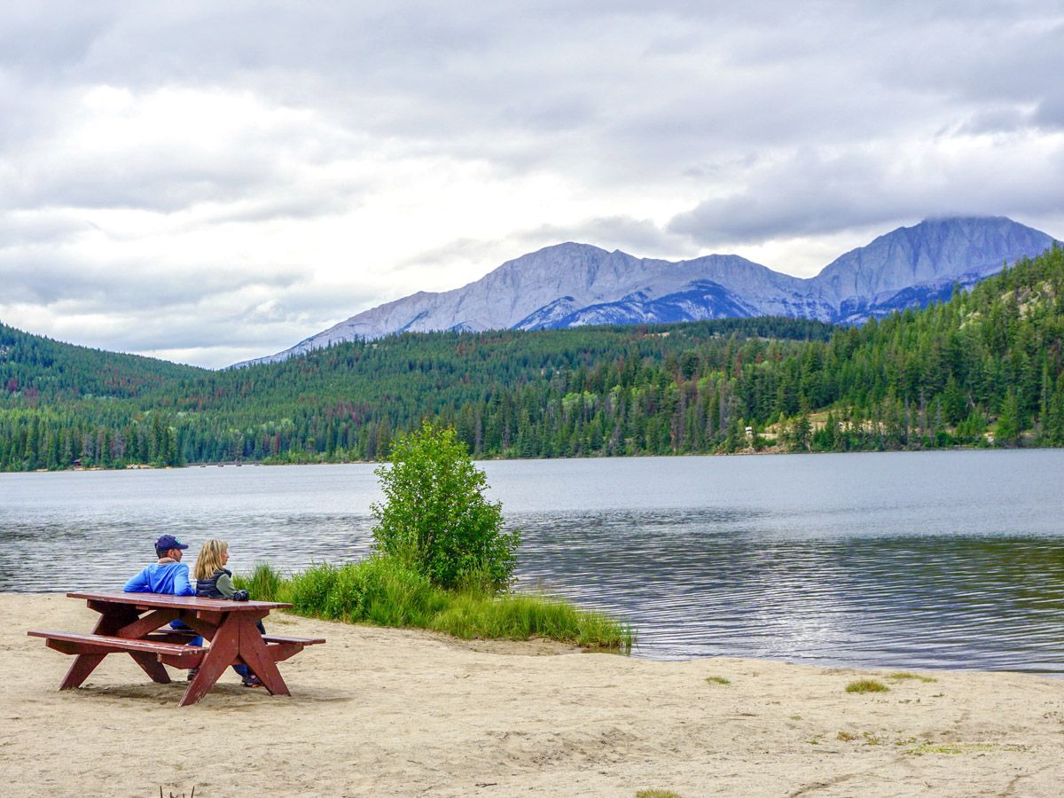 Couple resting on a bench on the Pyramid Lake Hike in Jasper National Park, Alberta