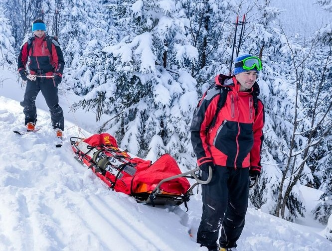 Ski patrol with sled helps to keep hikers safe in winter