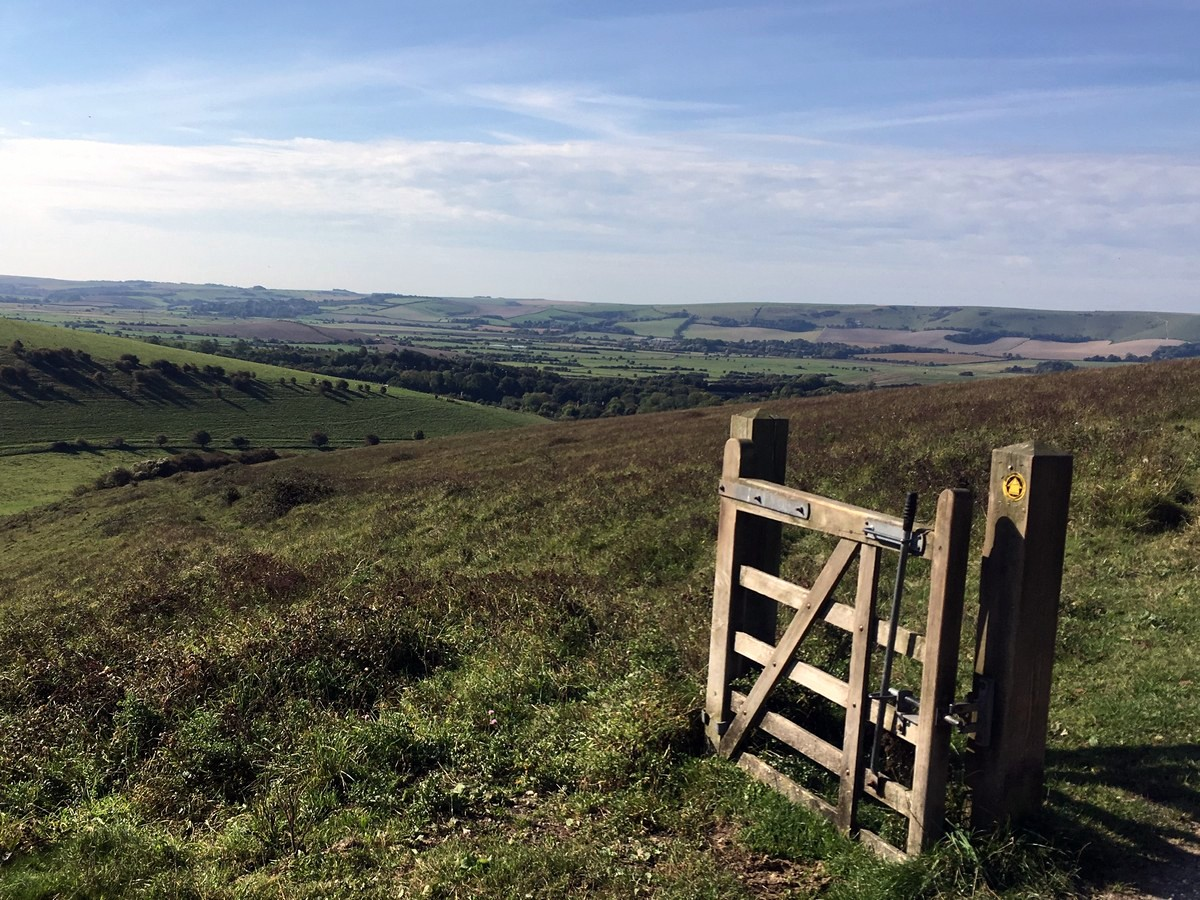 The gate with no fence with views towards Lewes from the Glynde and Mount Caburn Hike in South Downs, England