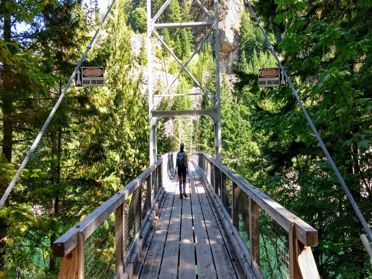 Hiking across the suspension bridge on the Diablo Lake Trail Hike in North Cascades National Park, Washington