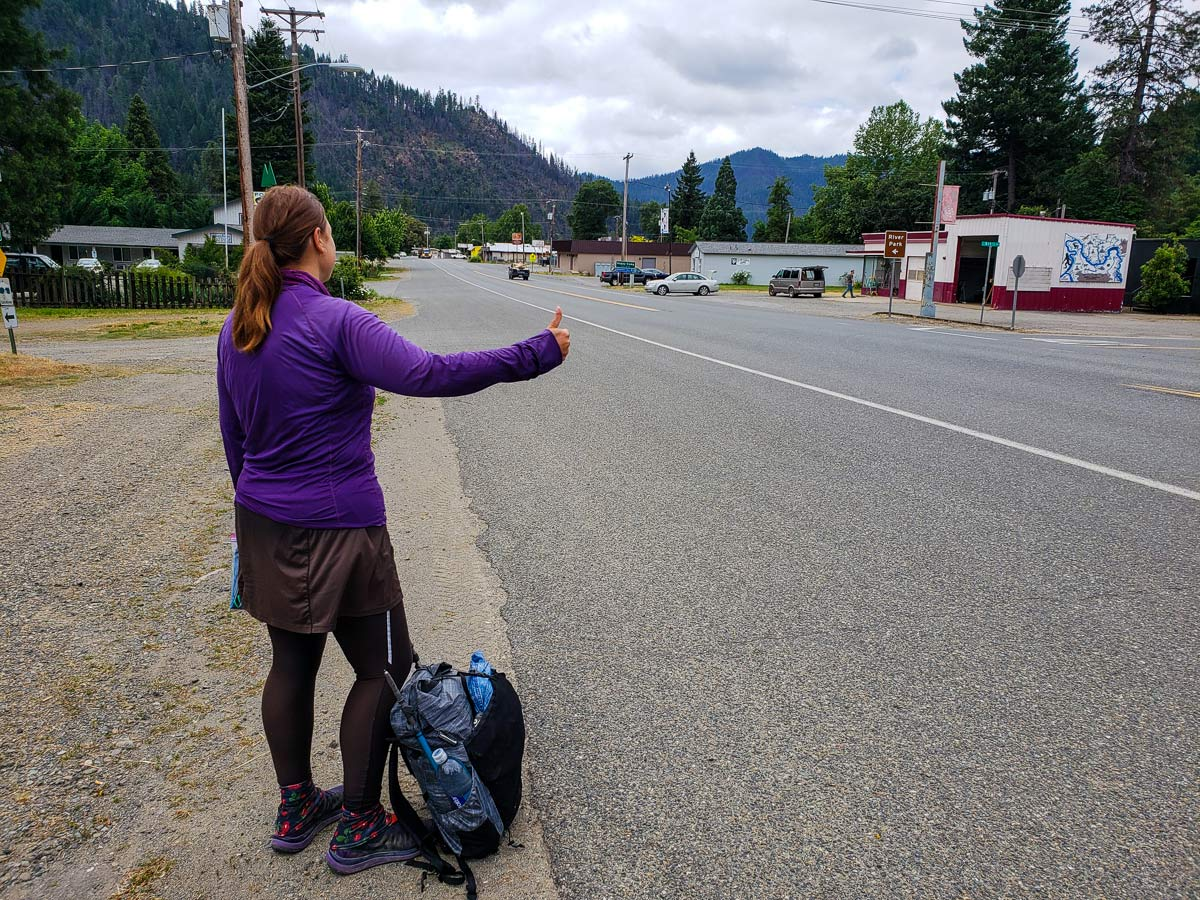 Hiker hitchhiking on the side of the road on the Pacific Crest Trail