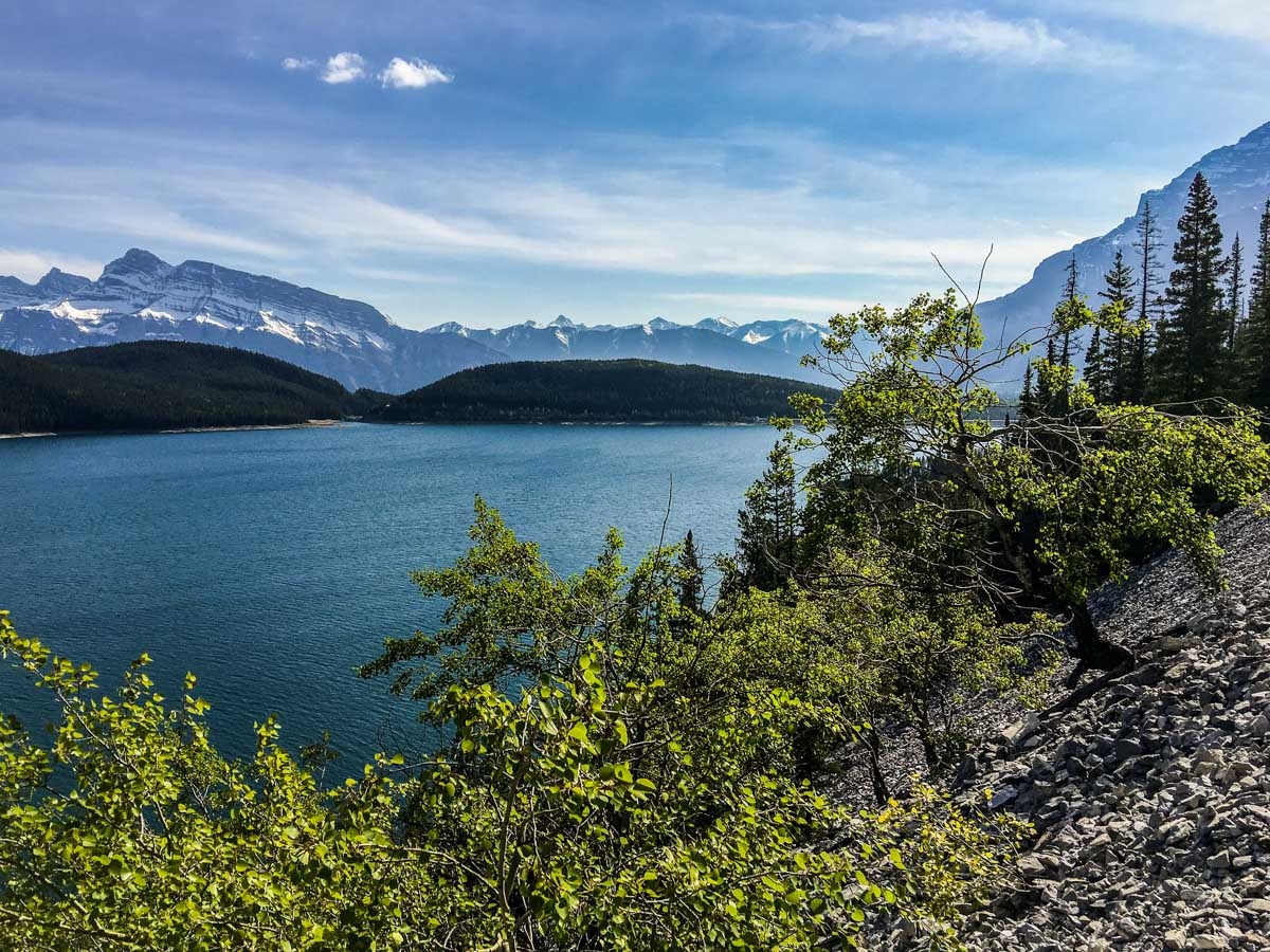 Lake surrounded by mountains on Lake Minnewanka backpacking trail in Banff National Park