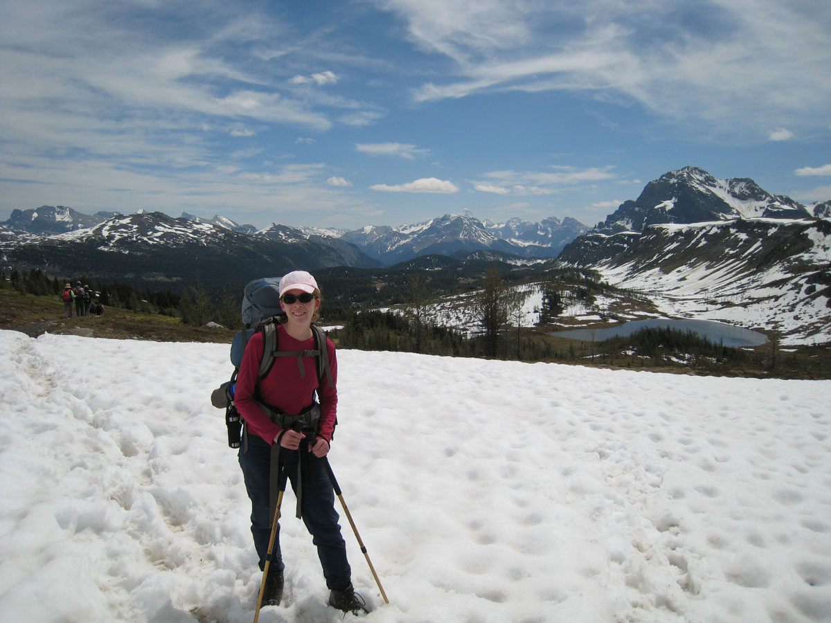 Lady hiking on snow on Egypt Lake backpacking trail in Banff National Park