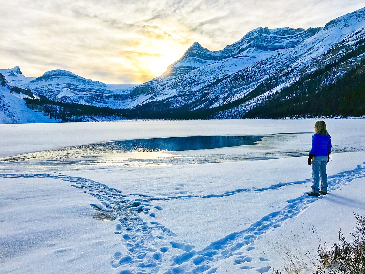Almost frozen lake on Bow Lake snowshoe trail in Banff National Park