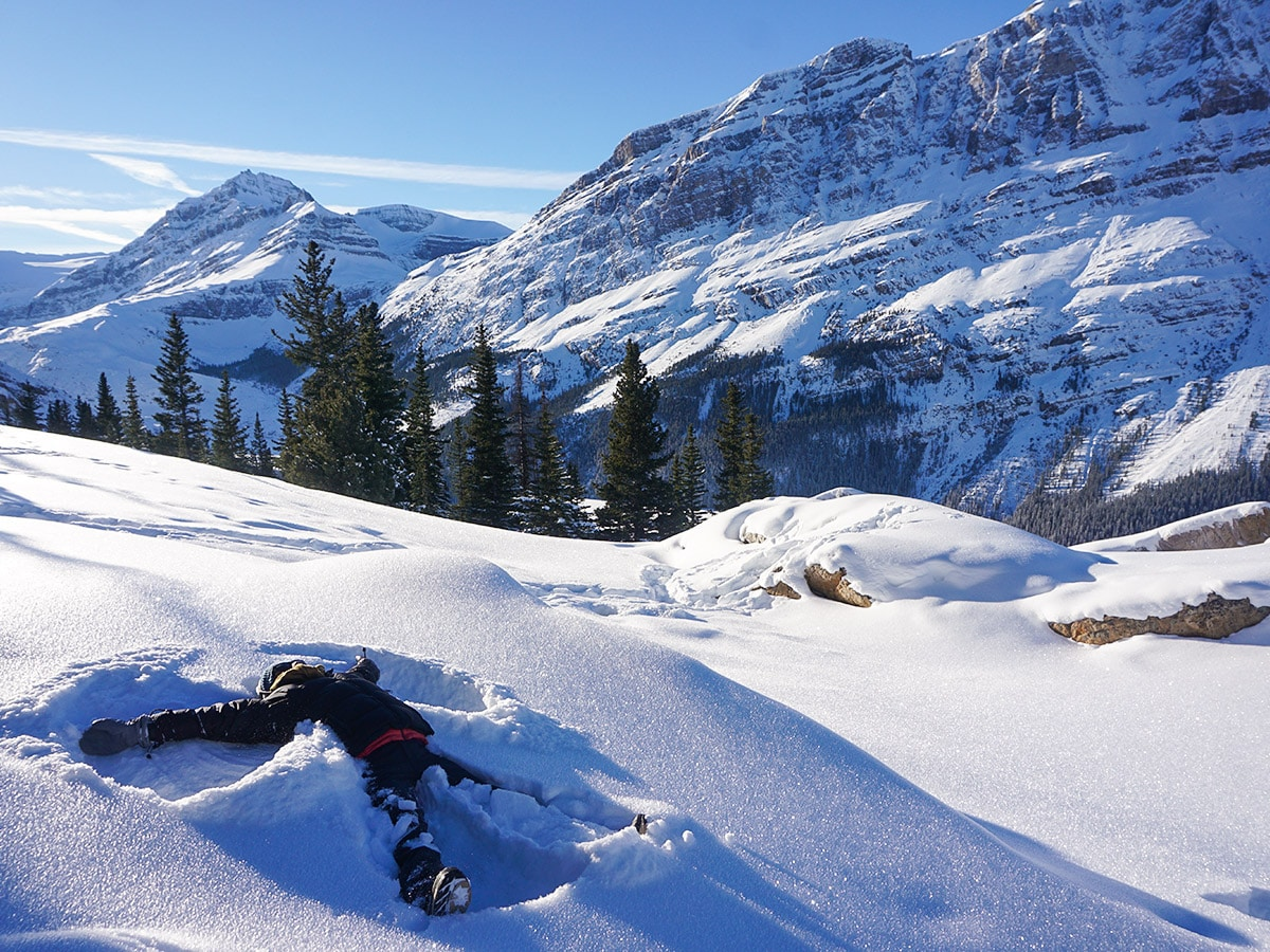 Making snow angels on Peyto Lake Viewpoint snowshoe trail in Banff National Park