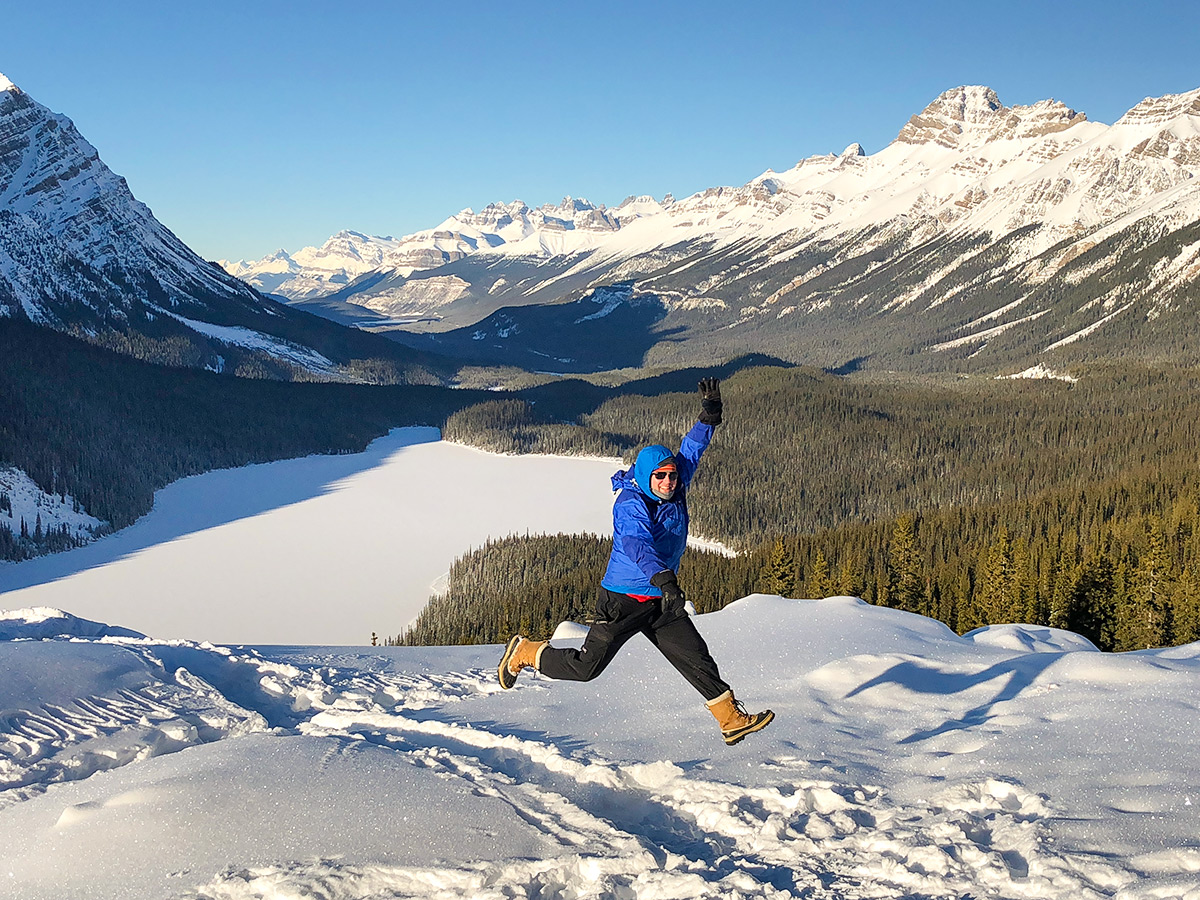 Lady enjoying the snow on Peyto Lake Viewpoint snowshoe trail in Banff National Park