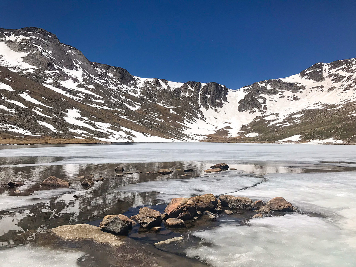 Lake getting covered by ice on Mount Evans hike in Denver, Colorado