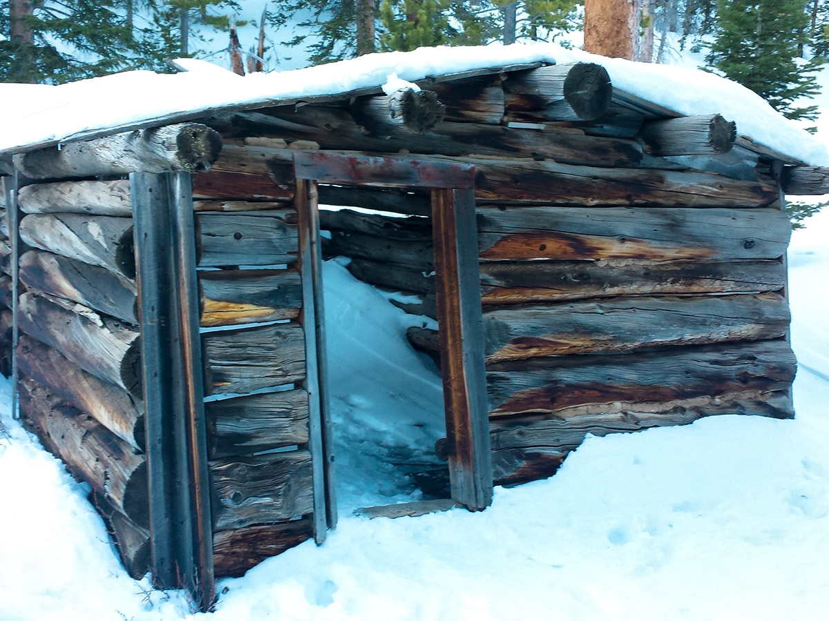 Log houses on St. Mary's Glacier hike in Denver are full of snow