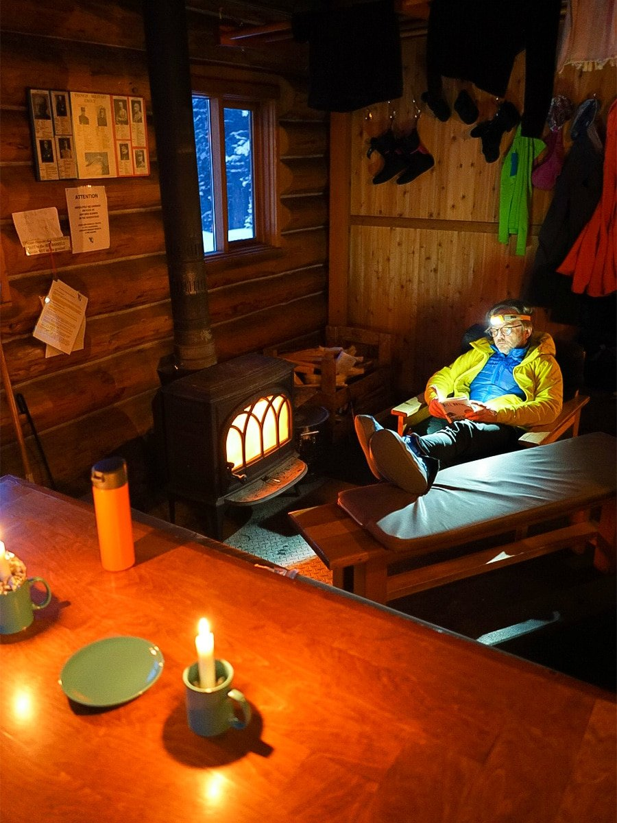 Reading and candlelight at Elk Lakes Cabin