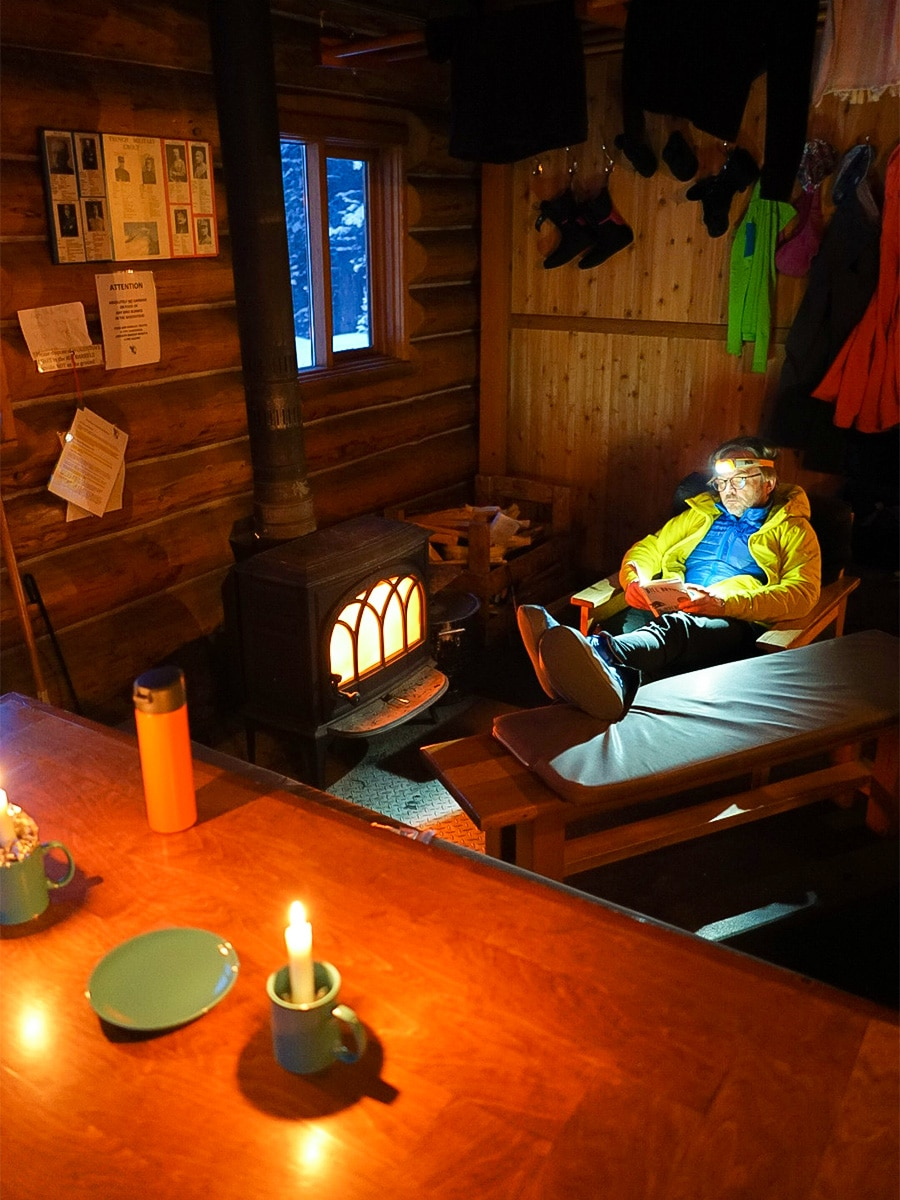 Reading and candlelight at Elk Lakes Cabin on Elk Lakes Backcountry Skiing Adventure