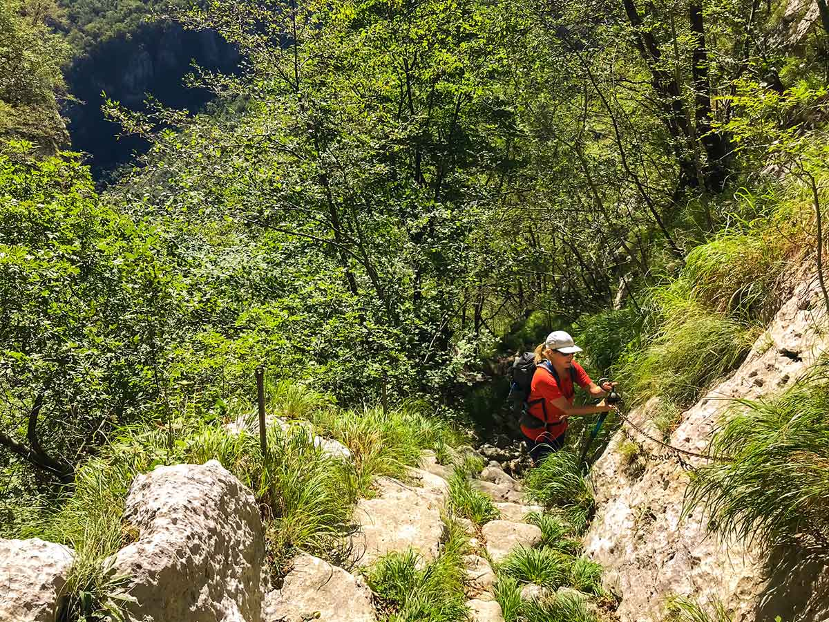 Hiker ascending with the help of chains on Monte Croce Hike in Tuscany