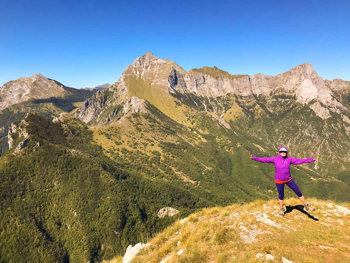 Hiker posing on top of Monte Croce Hike in Tuscany