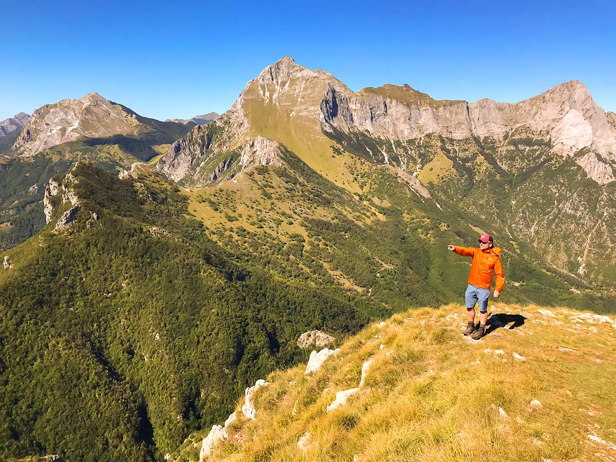 Biker posing among peaks on Monte Croce from Palagnana Hike in Tuscany