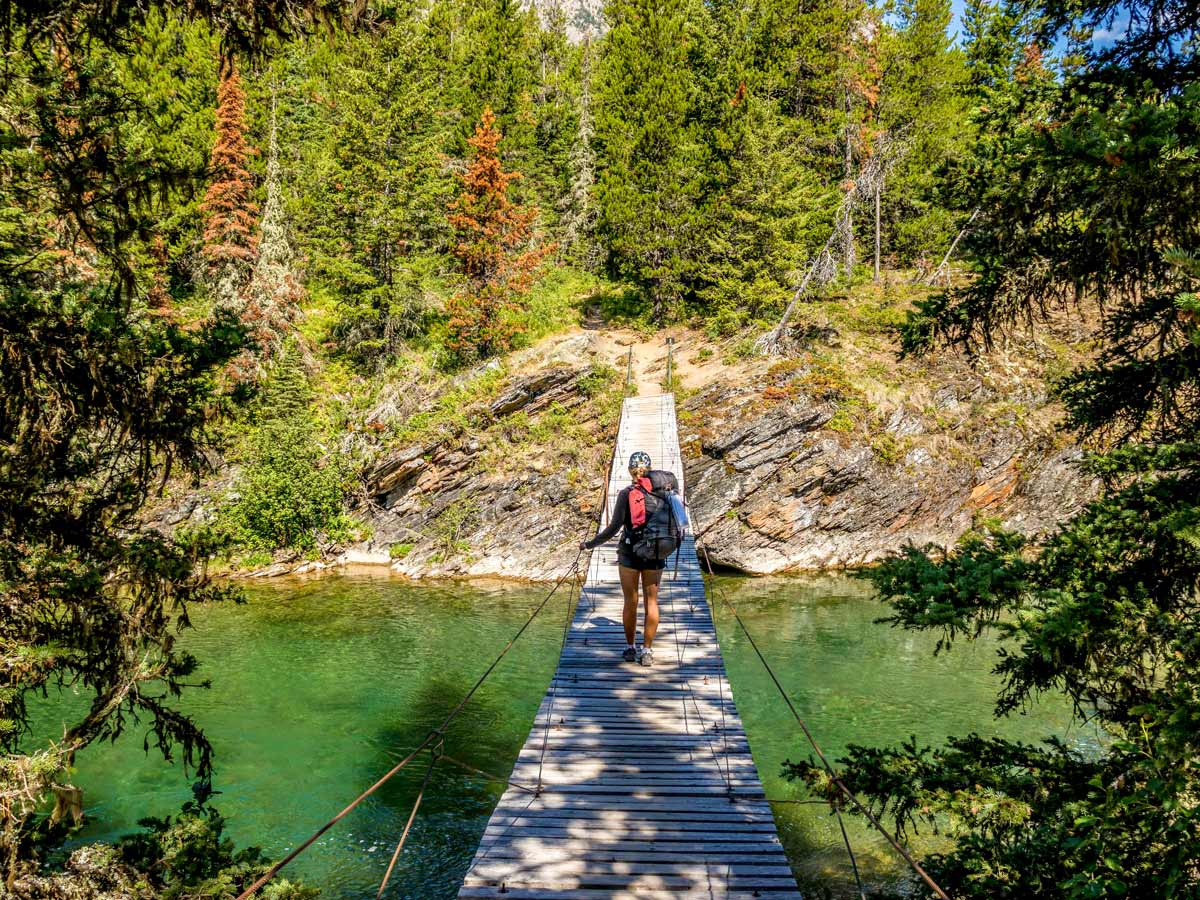 Crossing a suspension bridge on the backpack to Boulder Pass in Glacier National Park