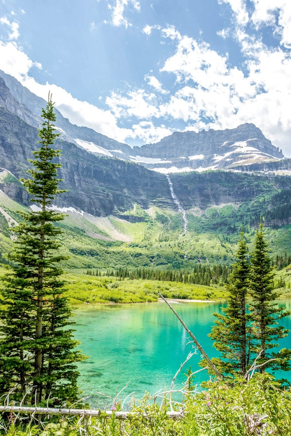 Beautiful turquoise lake with a waterfall on Boulder Pass Backpacking Trail in Glacier National Park