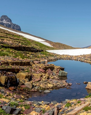 Snowy path of Boulder Pass Backpacking Trail in Glacier National Park