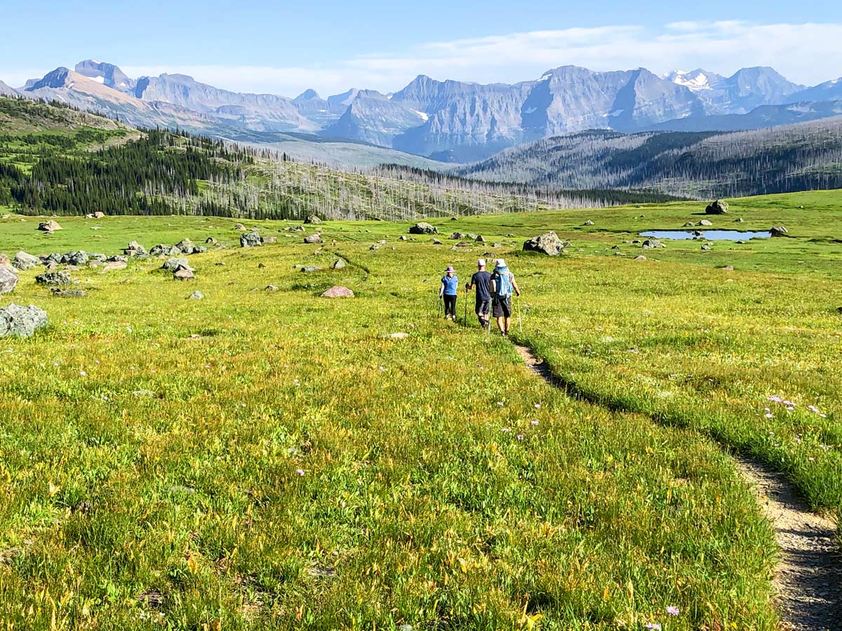 Hiking through the meadow surrounded by mountains on North Circle Backpacking Trail in Glacier National Park