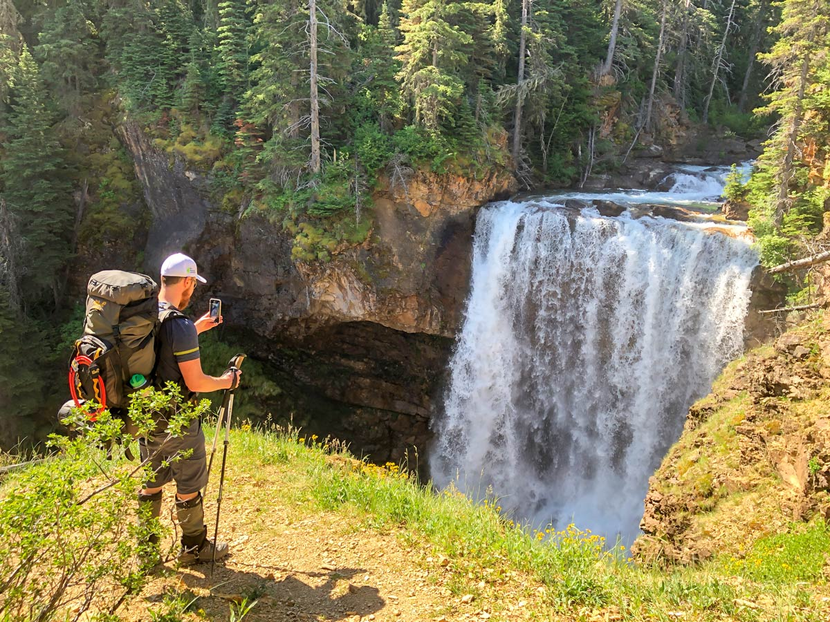 Taking pictures of beautiful waterfall on day 2 of hiking the North Circle Backpacking Trail in Glacier National Park