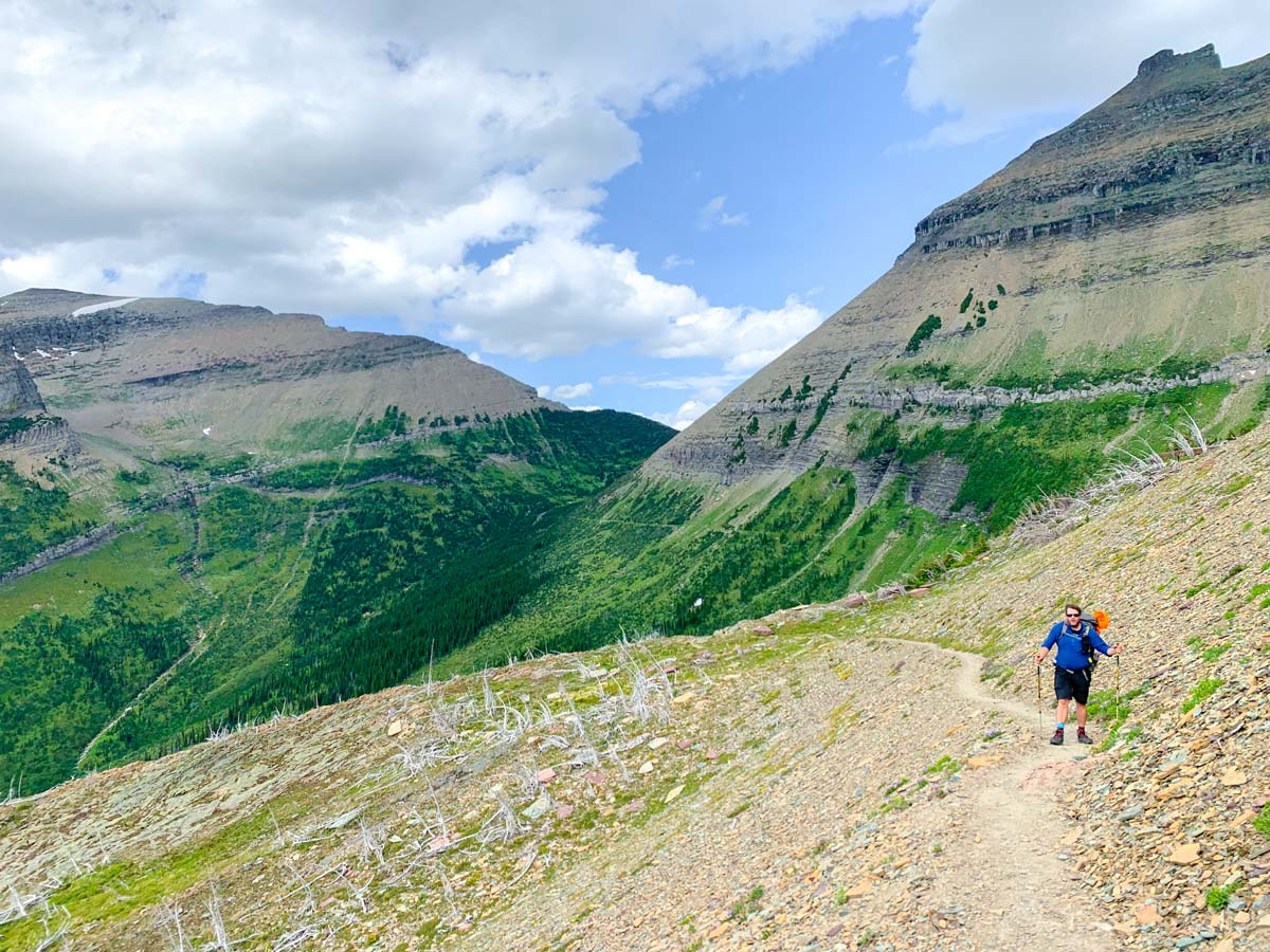 Hiker surrounded by beautiful peaks on North Circle Backpacking Trail in Glacier National Park