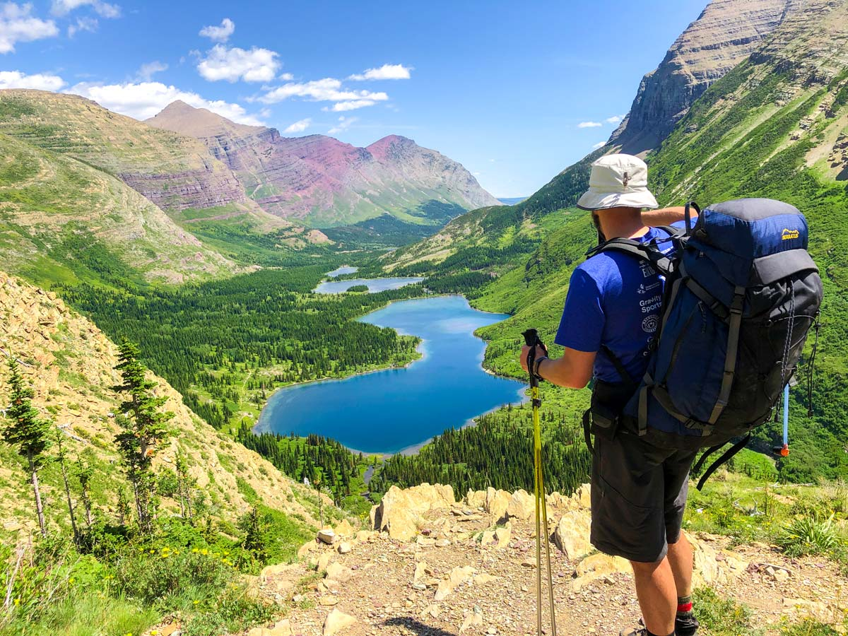 Hiker looking down on the Bullhead lake on North Circle Backpacking Trail in Glacier National Park