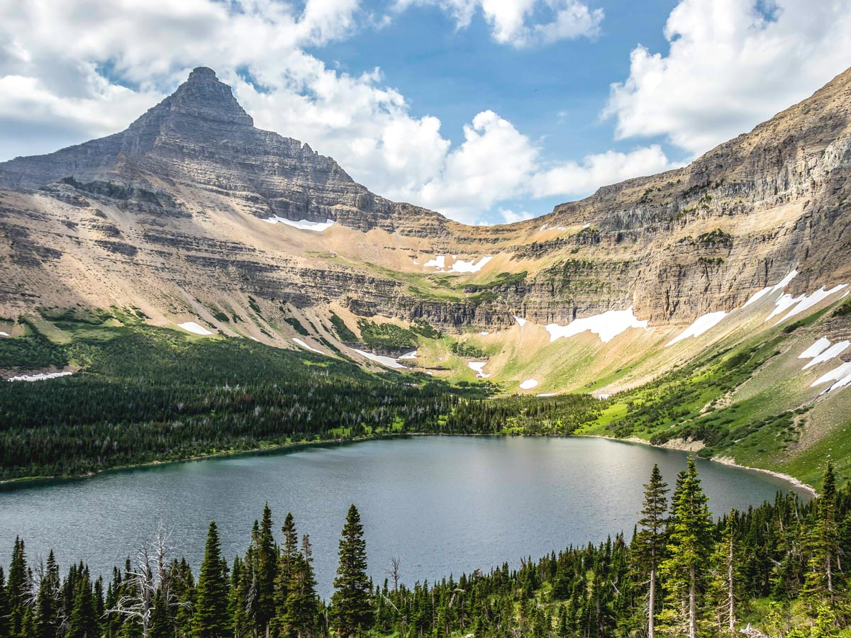 Lake surrounded by peaks on Pitamakan Dawson Loop Backpacking Trail in Glacier National Park