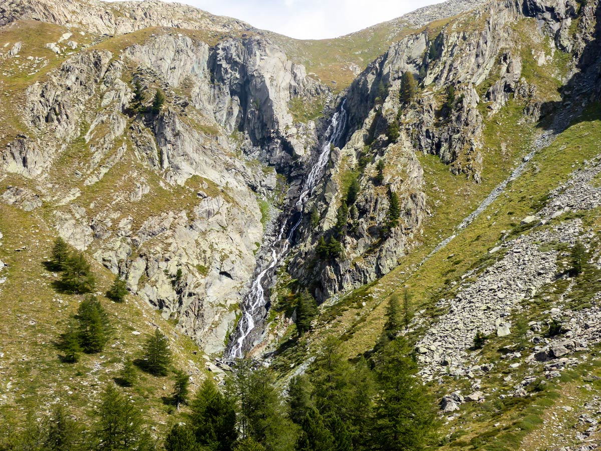Scenic waterfall on Lago di Loie hike in Gran Paradiso National Park, Italy