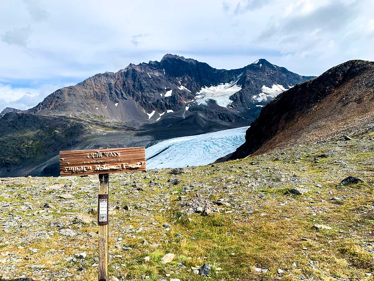 Sign on Crow Pass Trail looking towards Raven Glacier in Chugach State Park Alaska