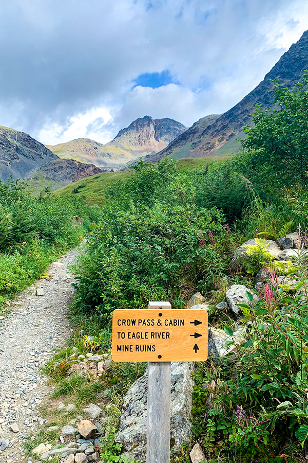 Sign pointing to Crow Pass on a trail to Raven Glacier Alaska