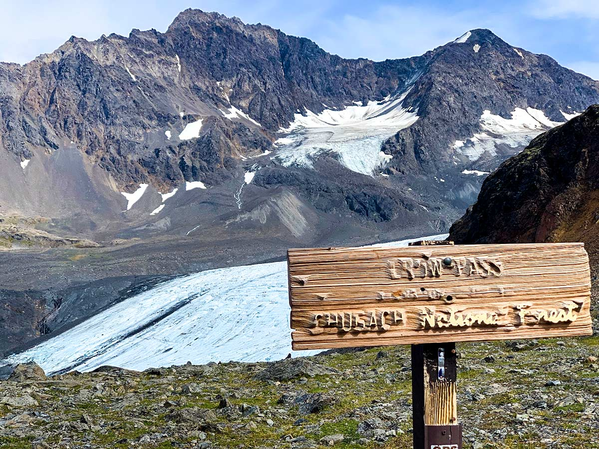 Crow Pass Trail signpost in front of Raven Glacier near Anchorage