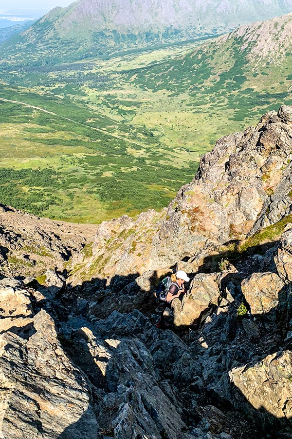 Hiker on a scrambly part of Flattop Mountain Trail near Anchorage Alaska