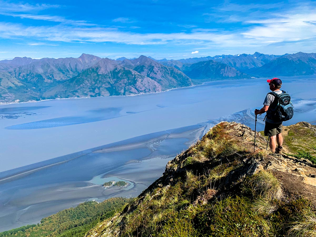 Hiker on an overlook to Turnagain Arm on Hope Point Trail in Kenai Mountains
