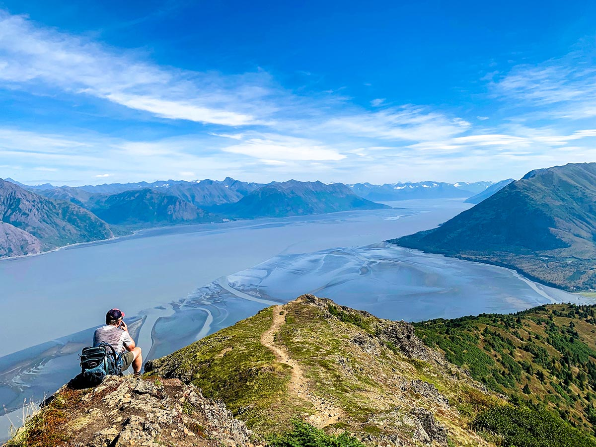 Hiker resting on Hope Point Trail with beautful views of Turnagain Arm in Alaska