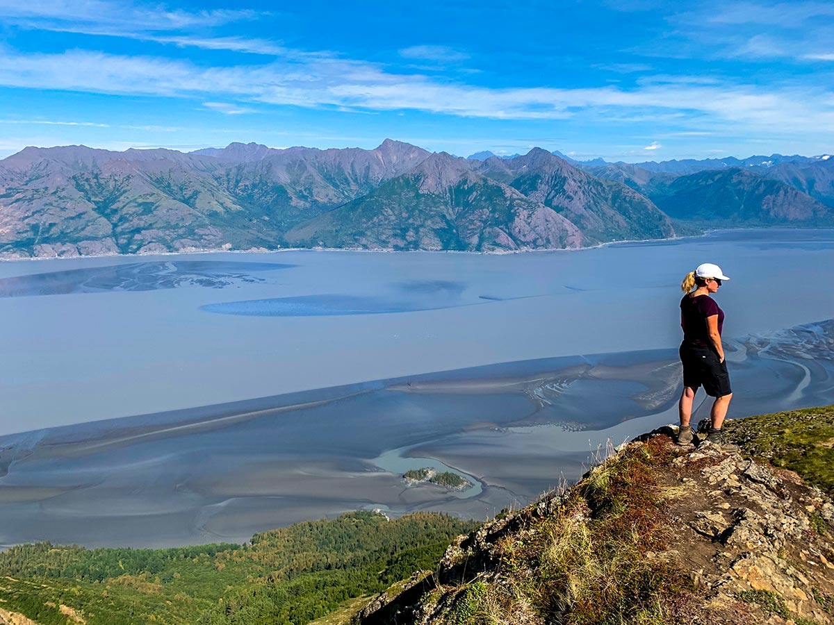 Hiker posing on overlook to Turnagain Arm on Hope Point Trail in Alaska