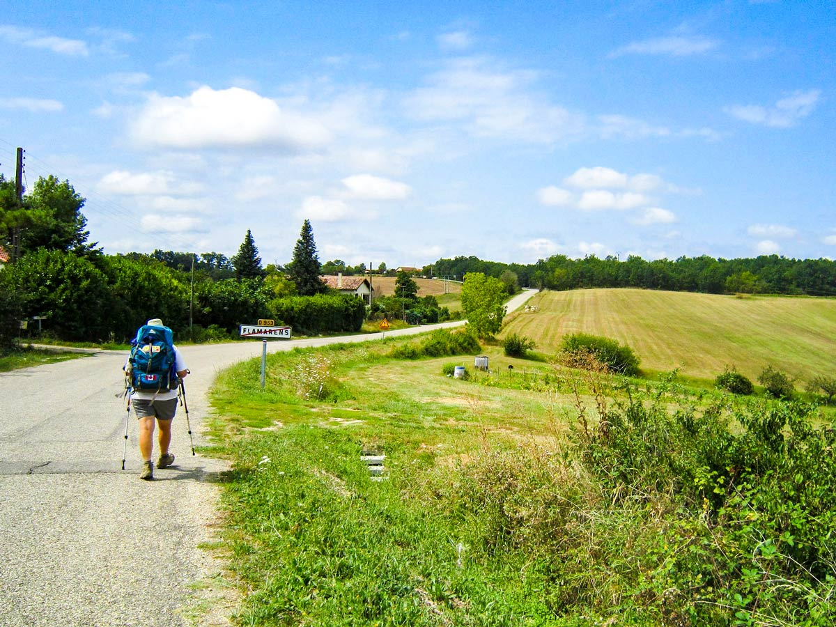Lone hiker departing the village on Camino de Santiago French Way full trek