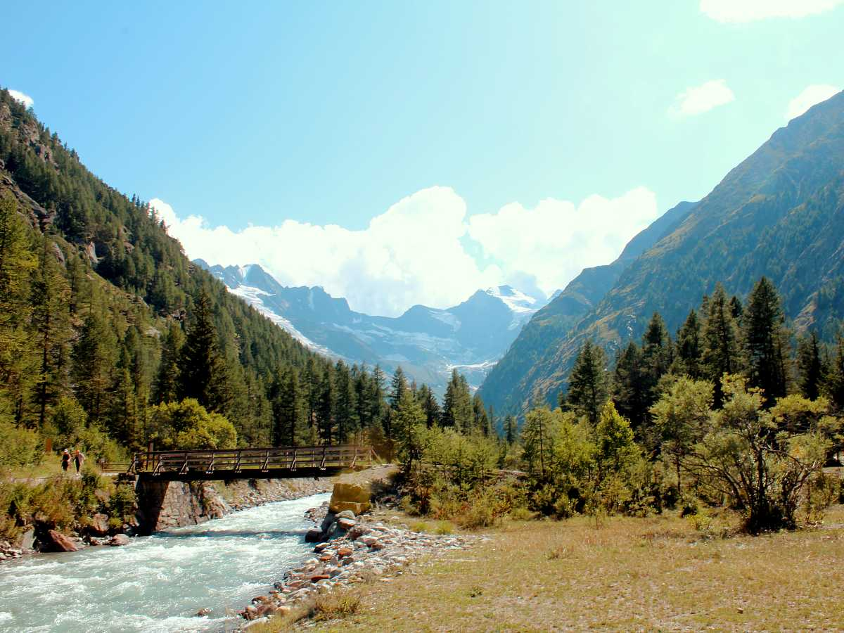 Walking along the Valnontey River with the highest peaks of Gran Paradiso National Park behind