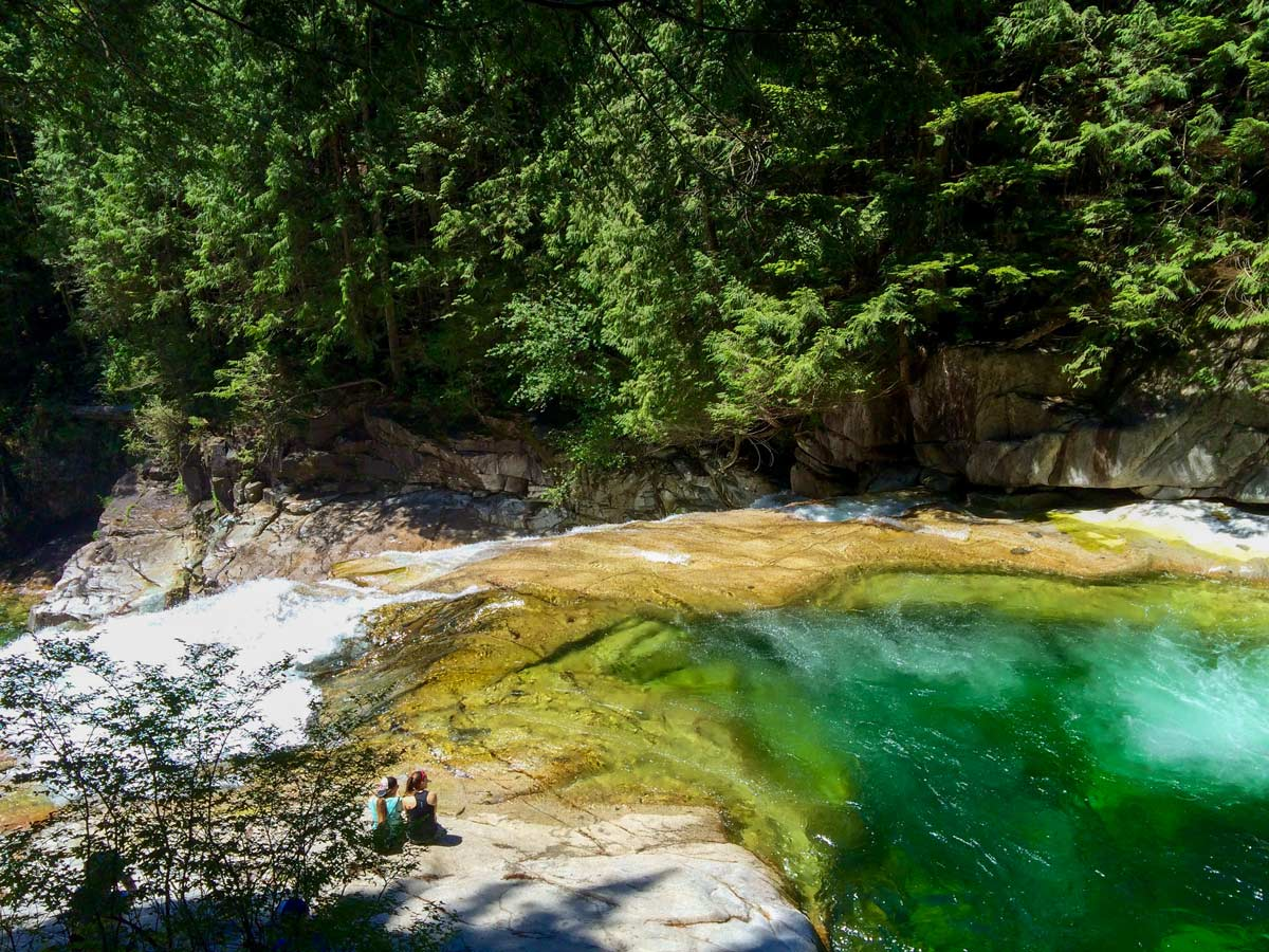 Hikers admiring turquoise waters of pools above Gold Creek Falls near Vancouver