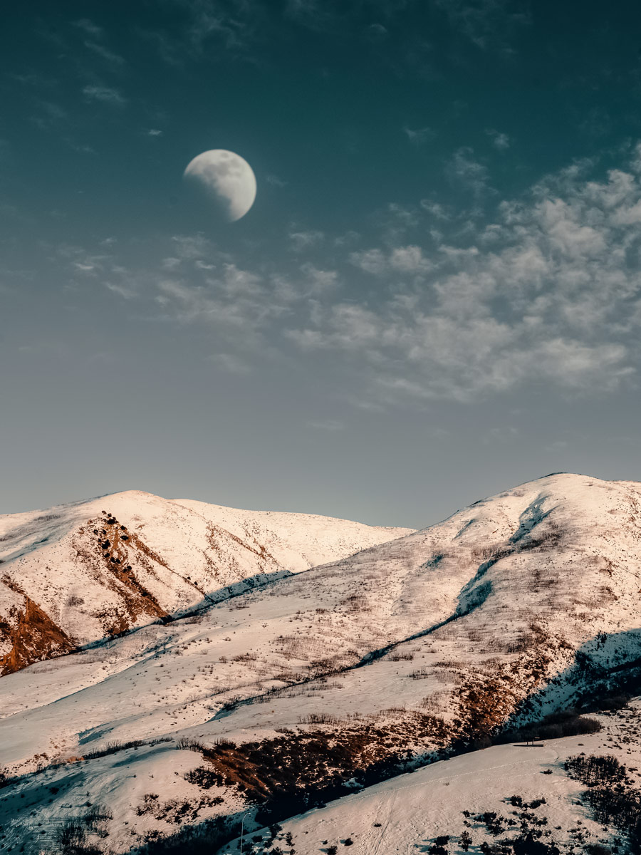 Afternoon moon sun over snowy hill mountains in Utah winter near Salt Lake City SLC