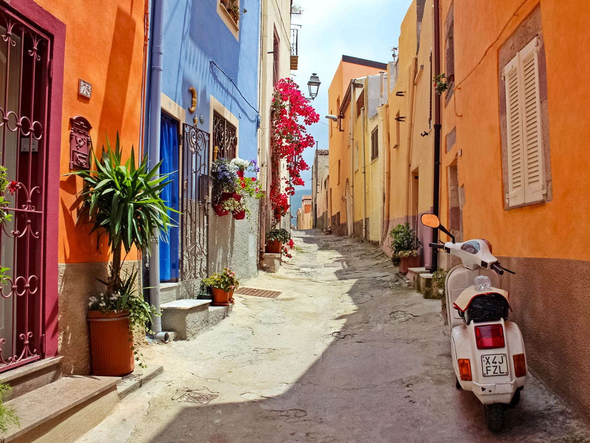 Moped bike on cobblestone street between colourful houses in italy