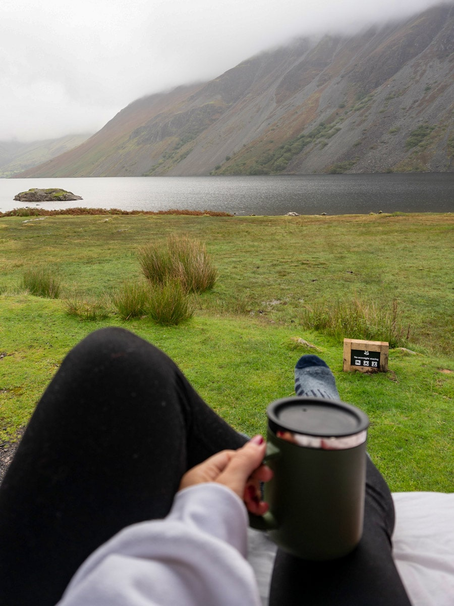 Morning coffee camping by fog mountains water shore in the UK Lake District