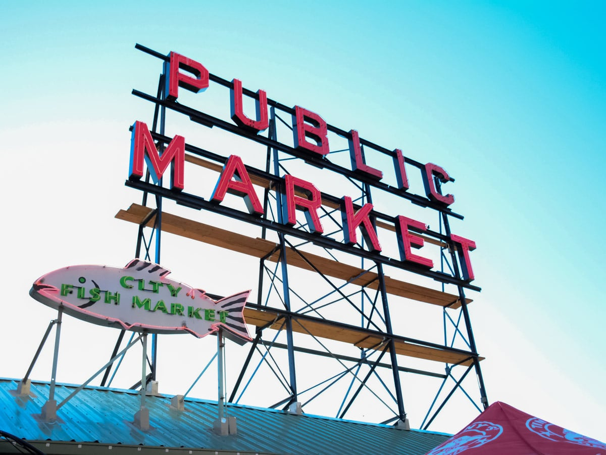 Pike Place Public Market sign on Seattle docks by the Pacific ocean