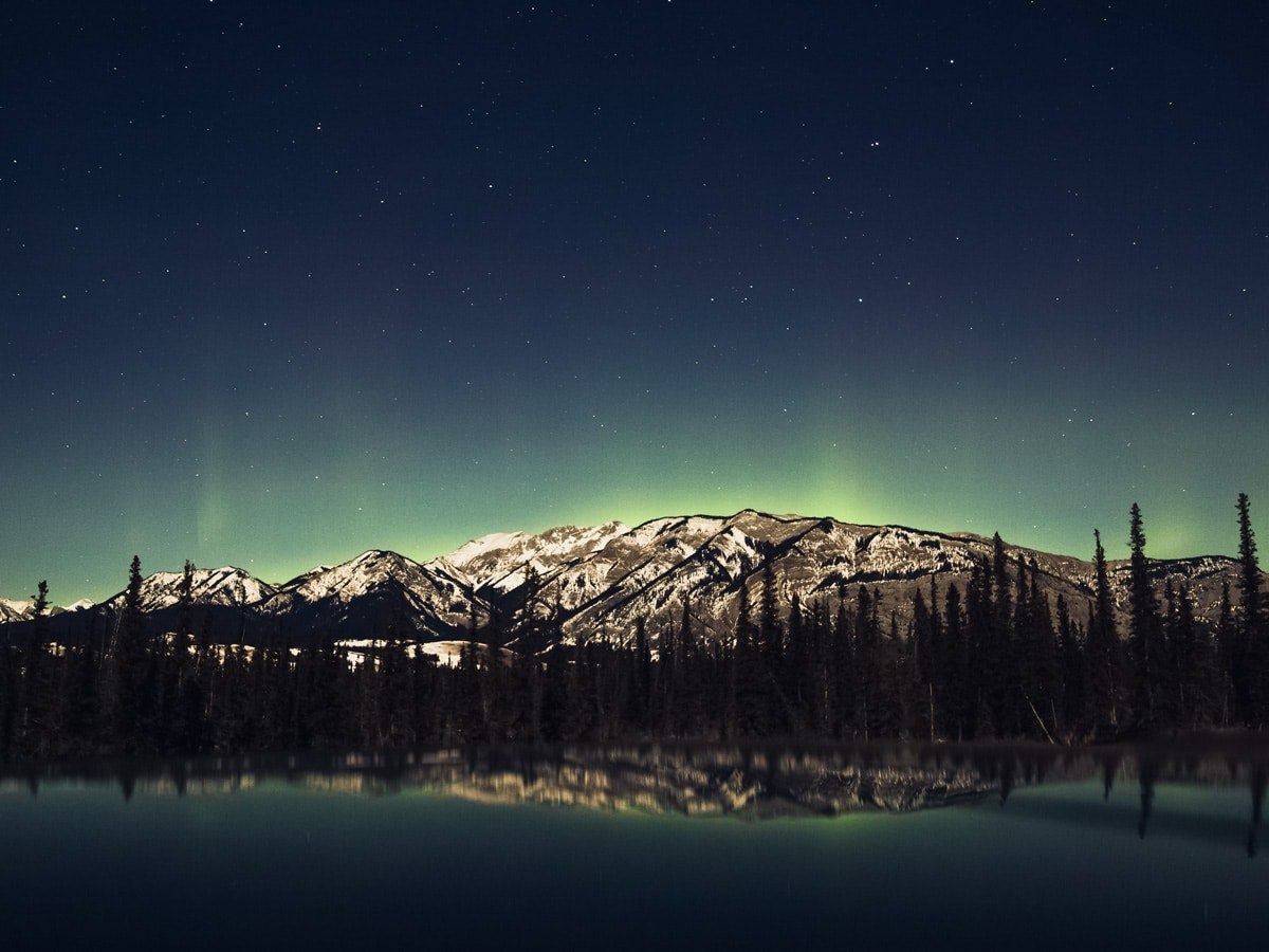 Starry night and Northern Lights over rocky mountains in Jasper Alberta Canada